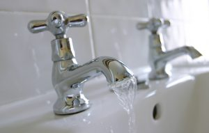 hot and cold taps of a sink, with water running out of one side