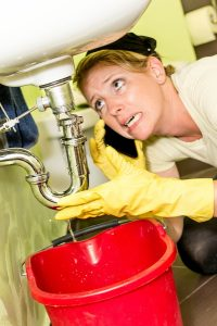 Female homeowner trying to catch water in a bucket from an under sink plumbing leak