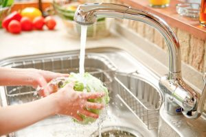 person washing head of lettuce in kitchen sink