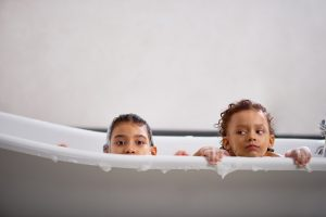 two-children-peeking-out-of-bathtub